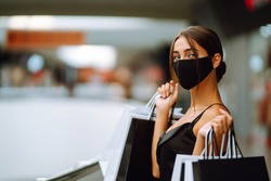 Young woman in protective black medical mask on her face with shopping bags in the mall. Purchases, black friday, discounts, sale concept. Covid-2019.