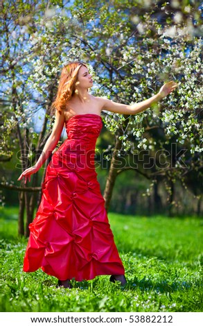 Young woman in red dress in cherry garden.
