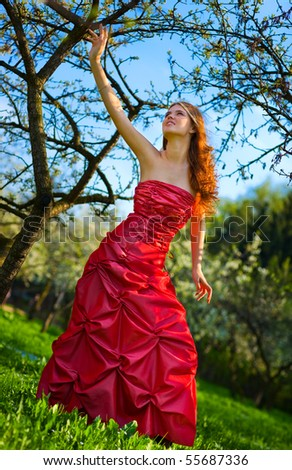 Young woman in red dress in cherry garden. Camera angle view.