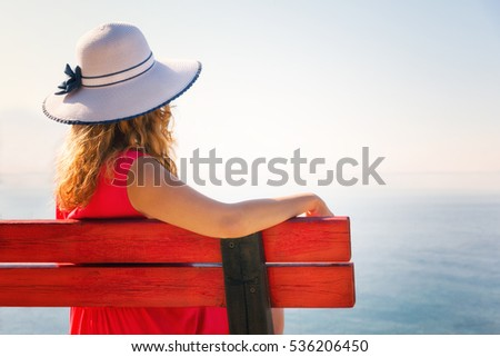 Young woman in red dress, siting on the bench and looking to the horizon.