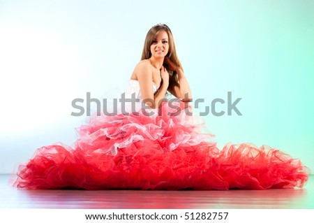 Young woman in red dress sitting on a floor.