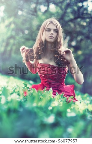 Young woman in red dress sitting on grass and looking aside.