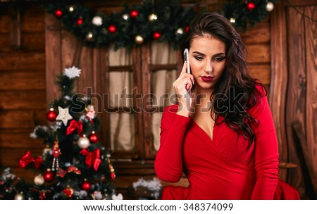 Young woman in red  dress  talking on mobile phone at Christmas decorated home #348374099