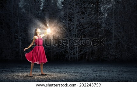 Stock Photo Young woman in red dress walking in night wood