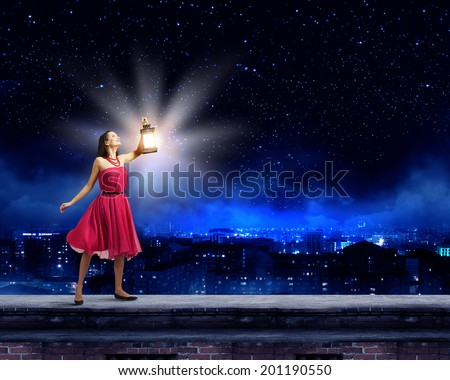 Stock Photo Young woman in red dress with lantern