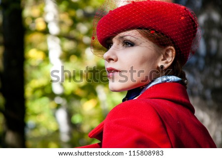 Young woman in red hat and red coat looking at something. - stock photo