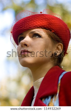Young woman in red hat and red coat looking in the sky