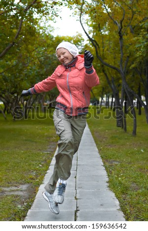 Young woman in red jacket jumps and have a fun in the park