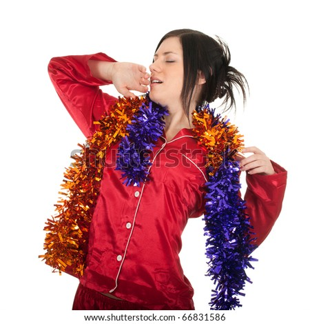 young woman in red pajamas and Christmas chains yawning and stretching