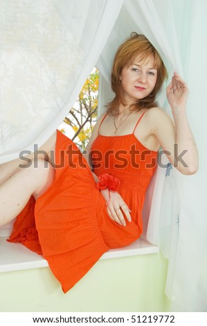 Young woman in red summer dress sitting on the windowsill