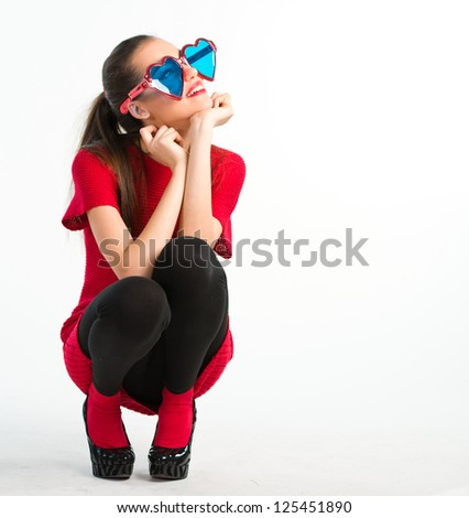Young woman in red with heart shaped glasses over a white background