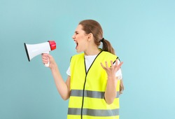 Young woman in reflective vest shouting into megaphone on color background