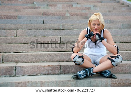 Young woman in roller skates sitting on the stairs