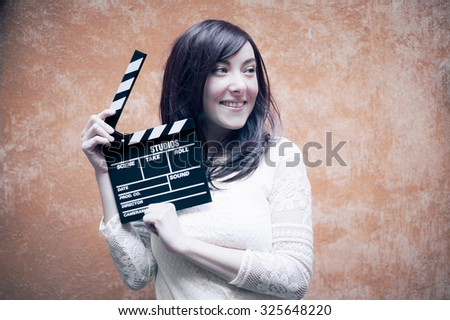 Young woman in 70s hippie style smiling with clapperboard, outdoor orange wall background #325648220