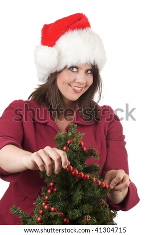 Young woman in Santa hat decorates a Christmas tree with red beads; isolated on a white background.
