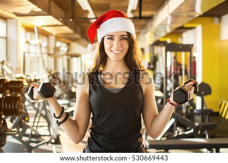 Young woman in Santa hat holding dumbbells at gym. New Year. Christmas, holidays, fitness, and gym concept.