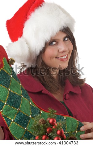 Young woman in Santa hat holds a Christmas stocking near a decorated Christmas tree: close-up and isolated on a white background.