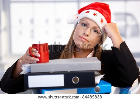 Young woman in santa hat sitting in office leaning on folders, exhausted, taking a break.?