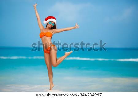 Young woman in santa hat sitting on beach. Christmas vacation. Christmas beach vacation travel woman wearing Santa hat and bikini enjoying christmas on tropical beach. woman in santa hat and bikini