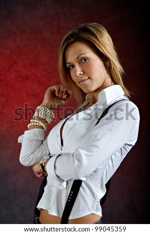 Young woman in sexy clothes with suspenders posing on dark background