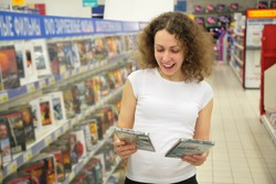 young woman in shop chooses disk