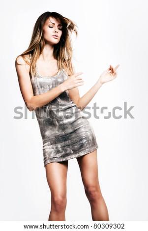 young woman in short dress dancing, studio shot