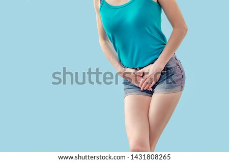 Young woman in shorts and a T-shirt is experiencing pain in the womb, pressed her hands to the lower abdomen. Medical concept. Gynecological problems.
