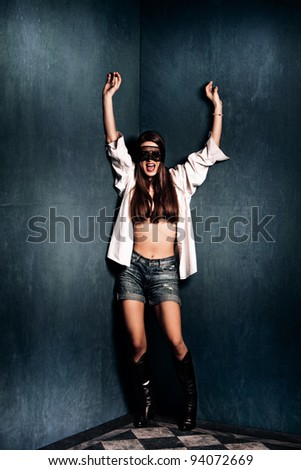 young woman in shorts, boots and lace over eyes stand with hands up screaming in corner of grunge room