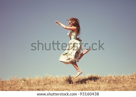 young woman in silk dress on top of the hill jumps, sky in background, retro colours, grain added