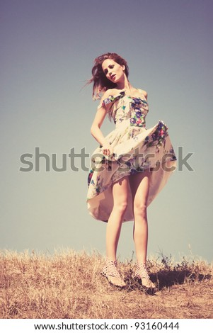 young woman in silk dress on top of the hill  sky in background, retro colours, grain added