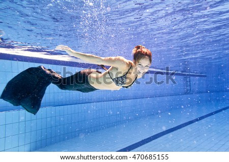Young woman in siren costume swimming in the pool