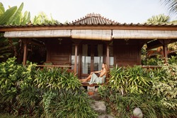 Young woman in sitting on a porch or veranda of wooden summer cottage or bungalow. Tropical summer vacation.