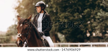 Young woman in special uniform and helmet riding horse. Equestrian sport - dressage. Сток-фото ©