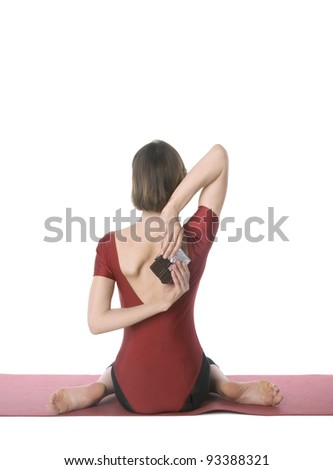 Young woman in sports clothes trying to hide a chocolate bar behind her back