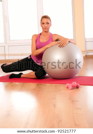 Young woman in sportswear, doing fitness exercise with fit ball.
