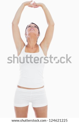 Young woman in sportswear holding hands up together over white background