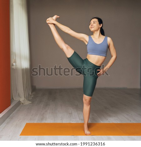 Young woman in sportswear, practicing yoga, standing on the mat in the studio, performs the Uttita hasta padangusthasana exercise Foto stock ©