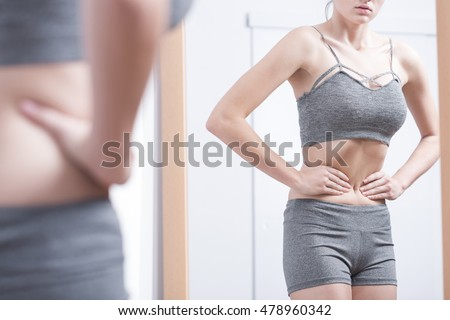 Young woman in sporty underwear looking at her refletion in the mirror Foto stock ©