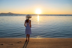 Young woman in straw hat and a dress standing alone on empty sand beach at sunset sea shore. Lonely female looking at horizon over calm ocean surface on vacation trip.