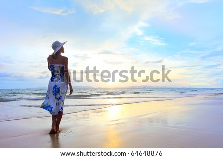 Young woman in straw hat standing on wet sand and looking to somewhere - stock photo