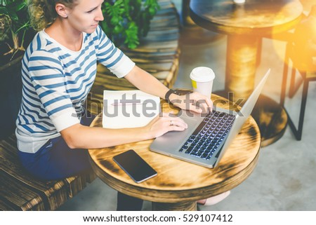 Young woman in striped t-shirt sitting at a round wooden table in cafe and using a laptop. On the table is a notebook, smatrfon and cup of coffee. Online training, interview. Girl uses the gadget.