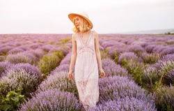 Young woman in stylish dress and hat looking away and walking amidst bushes of fresh lavender in evening in nature