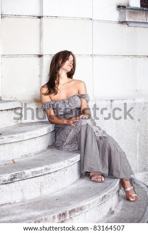 young woman in summer dress sit on stairs, waiting for someone, outdoor shot