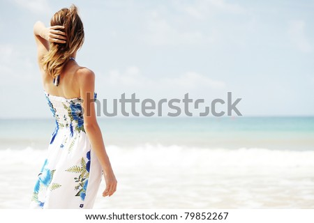 Young woman in summer dress standing by blue sea and looking to horizon