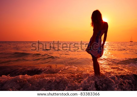 Young woman in summer dress standing on a rock and looking to a sea - stock photo
