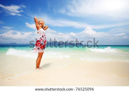 Young woman in summer dress standing on sand and holding straw hat