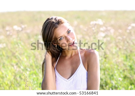 Young woman in summer dress walking on a meadow