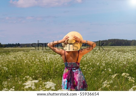 Young woman in summer hat enjoying nature