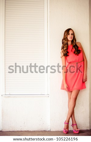 young woman in summer short dress lean on white wall outdoor shot day time