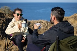 Young woman in sunglasses and brunette man holding iron mug cups and toasting, celebrating holidays spending together in nature landscape, sitting in chairs at top of cliff by blue sea on sunny day